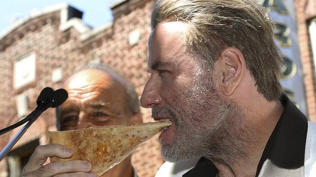 "But not John Travolta, he knows how it's done. Here the ""Gotti"" star is enjoying a slice of pizza from Lenny's Pizzeria in New York on Tuesday. The pizzeria was highlighted in the 1977 blockbuster ""Saturday Night Fever""."