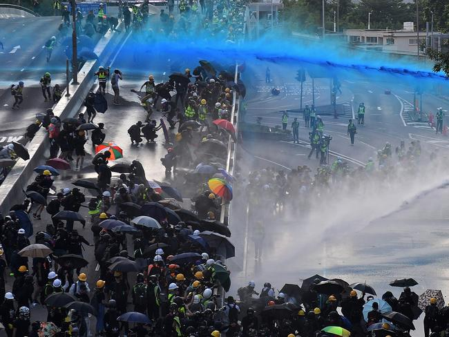 Pro-democracy protesters react as police fire water cannons outside the government headquarters in Hong Kong.