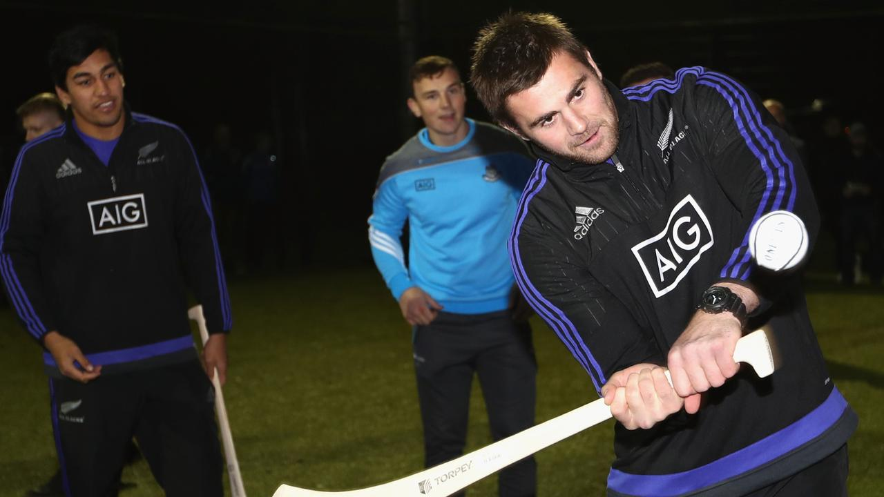 Liam Squire of the All Blacks tries the Irish sport of hurling at Castleknock College.
