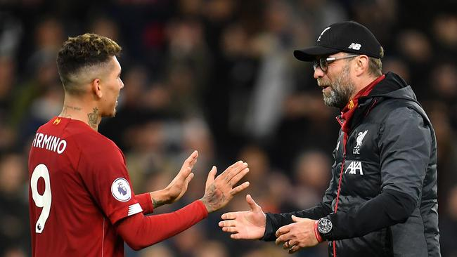 Jurgen Klopp (right) embraces Roberto Firmino following Liverpool's clash with Tottenham Hotspur.