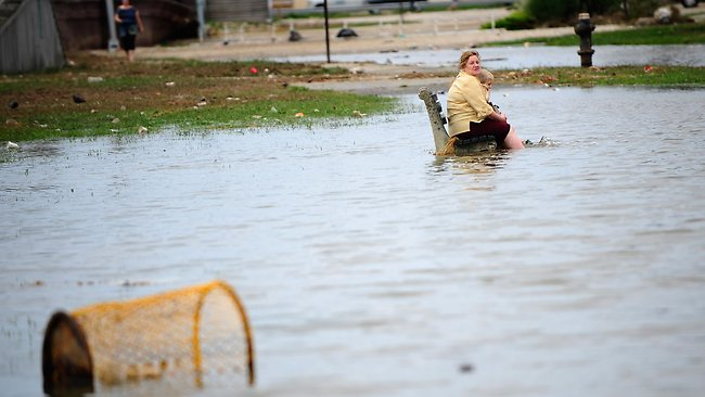 A woman and a child sit on a public bench amongst floodwater on Rockway Beach after Hurricane Irene swept through New York. Picture: Emmanuel Dunard / AFP