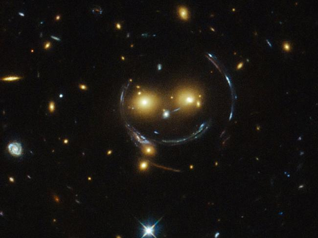 "The universe it laughing at us ... This ""smiley face"", recently snapped by the Hubble Space Telescope, demonstrates the effect of ""gravitational lensing"", where light is bent by gravity. Source: NASA/ESO"