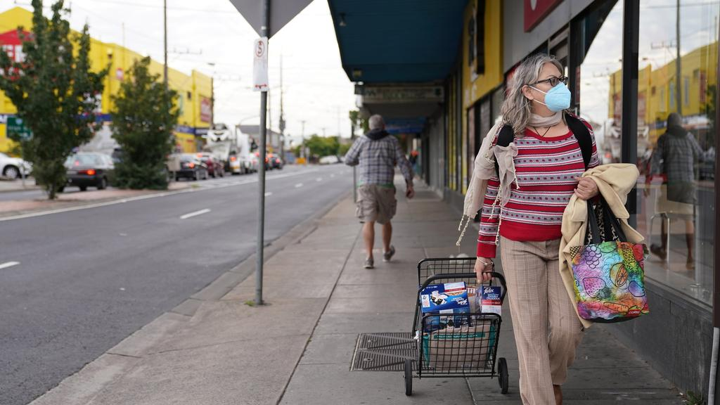 A woman walking home from the shops in Preston this morning. Picture: AAP Image/Stefan Postles