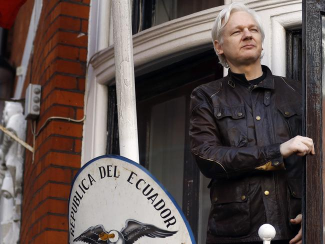 WikiLeaks founder Julian Assange looks out from the balcony at the Ecuadorian embassy where his possessions will be seized by prosecutors. Picture: AP Photo/Frank Augstein