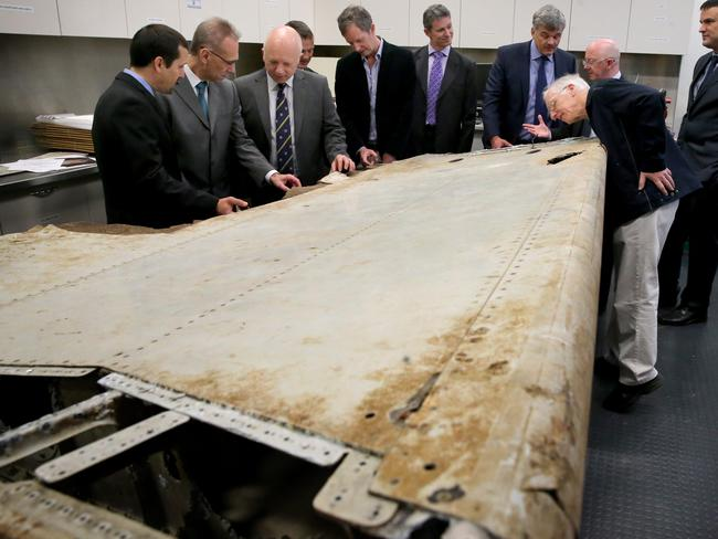 Visiting aviation and air safety experts examine the right outboard main wing flap from MH370 at the Australian Transport Safety Bureau (ATSB) in Canberra last year.