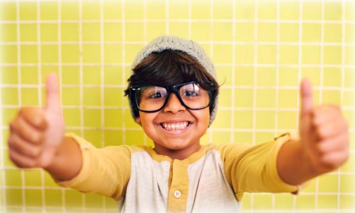 Shot of a cute little boy wearing glasses and a beanie showing thumbs up