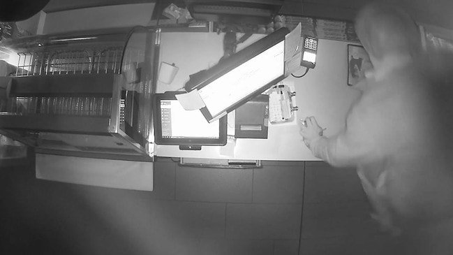 CCTV shows the man jump the counter after rifling through the cigarette counter. Picture: Queensland Police