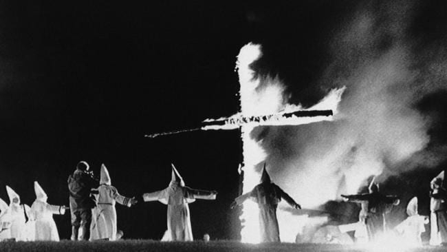Ku Klux Klan members wearing traditional robes form a circle around a burning cross in Rumford, Maine in 1987. Picture: AP Photo/Scott Perry
