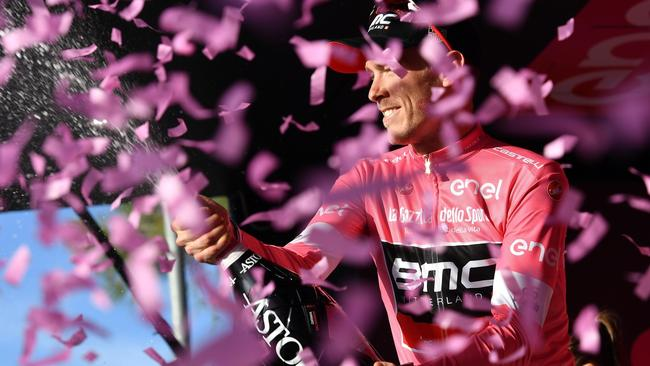 Rohan Dennis celebrates on podium after retaining the pink jersey.