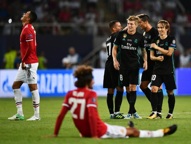 Toni Kroos of Real Madrid and Luka Modric of Real Madrid celebrate victory as Marouane Fellaini of Manchester United is dejected