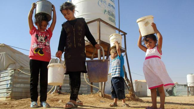 Children carry water in a refugee camp.