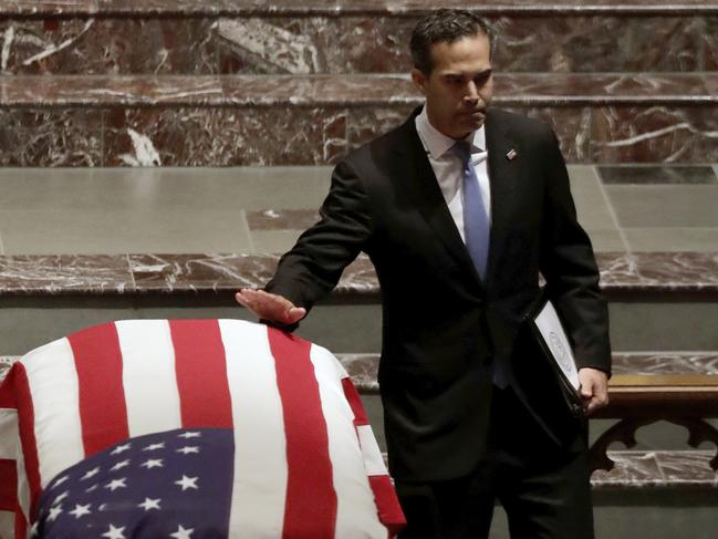 George P. Bush touches the flag-draped casket after giving a eulogy during a funeral for former President George H.W. Bush. Picture: AP