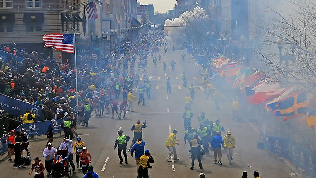 People react as an explosion goes off near the finish line of the 2013 Boston Marathon in Boston. Two explosions went off at the Boston Marathon finish line on Monday, sending authorities out on the course to carry off the injured while the stragglers were rerouted away from the smoking site of the blasts. (AP Photo/The Boston Globe, David L Ryan)