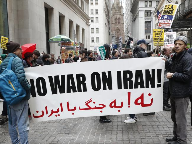 Protesters opposed to the US position on Iran hold a sign as they joined others from a variety of causes during a May Day rally in front of 40 Wall Street, a Trump-owned property in New York. Picture: AP