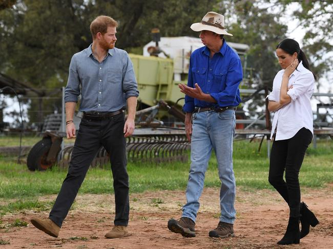Prince Harry (L) and Meghan chat with farmer Scott Woodley (C) during a visit to his family's drought-affected farm called Mountain View near Dubbo on October 17. Picture: Dean Lewins
