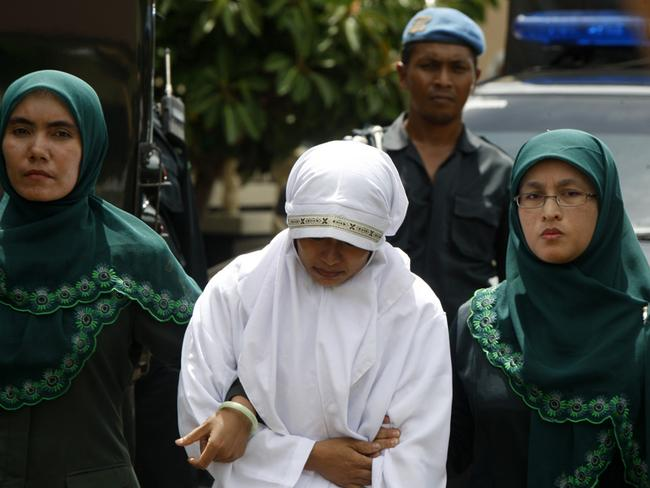 A woman is escorted on her way to be caned.