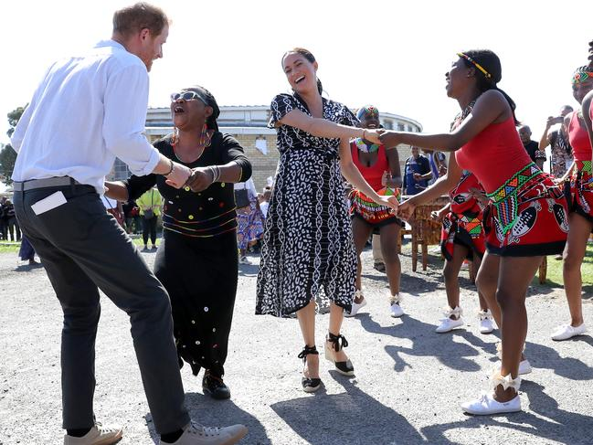 The couple are pulled into dancing with locals. Picture: Chris Jackson/Getty Images.