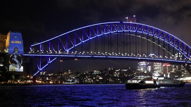 The Sydney Harbour Bridge lit up with the colours of each Everest runner for the barrier draw on Tuesday night. Picture: Christian Gilles