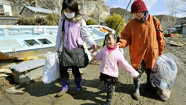 Members of a family retrieve clothes from their tsunami-wrecked home in Higashimatsushima, Miyagi Prefecture / AP