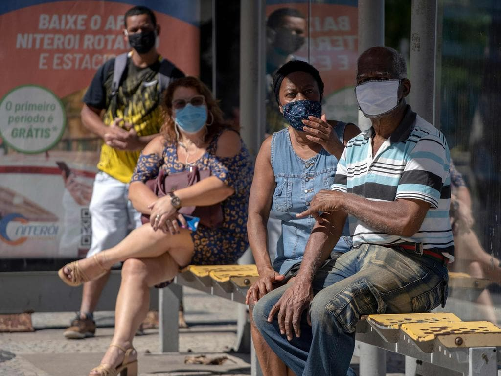 Locals wearing face masks wait for a bus during the first day of lockdown due to the COVID-19 in Rio de Janeiro. Picture: AFP