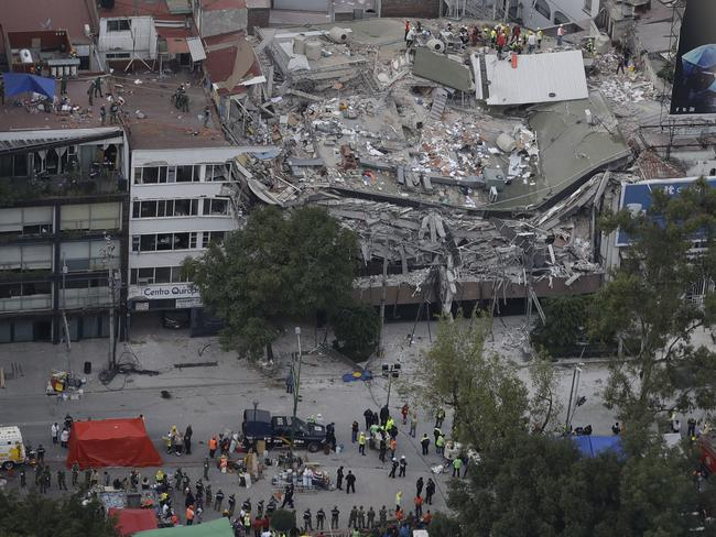 Rescue workers search for people trapped inside a collapsed building in the Roma Norte neighbourhood. Picture: Rebecca Blackwell/AP