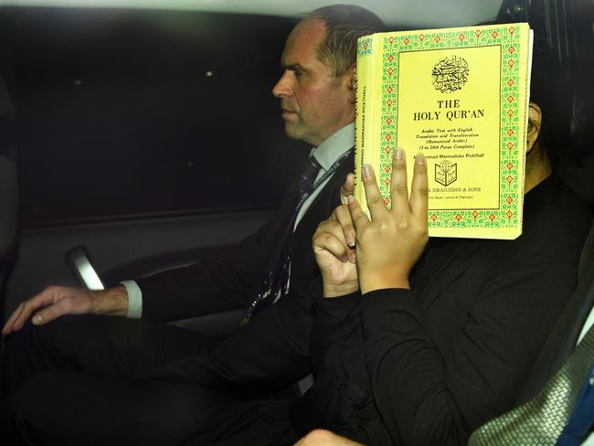 The 22-year-old covers her face with a copy of the Quran while being driven between two detectives. Picture: Mike Keating