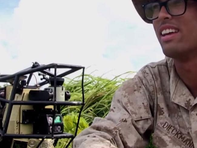 """Plastic pals ... A US Marine sits with the """"Alpha Dog"""" legged support robot during testing in Hawaii."""