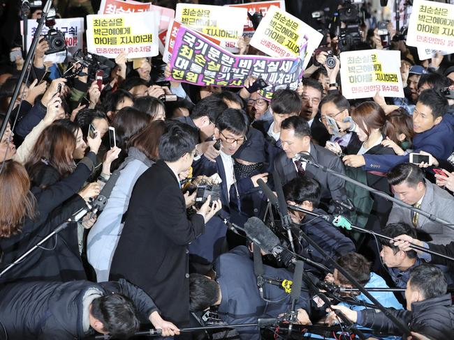 Choi Soon-Sil, centre, surrounded by media, officers and protesters. Picture: Lee Jin-man/AP