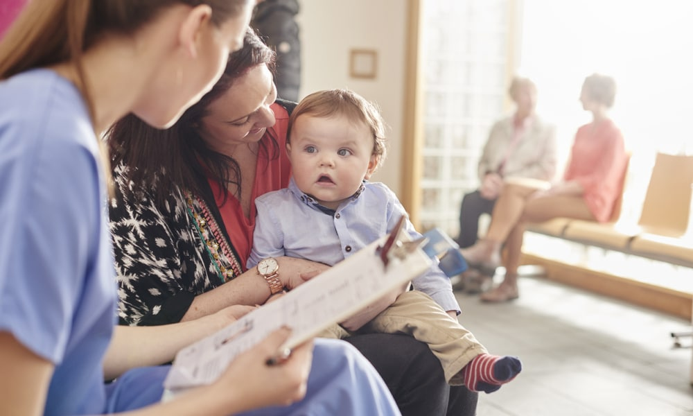 a female nurse sits next to a woman and her baby son in the waiting room of a clinic and casually chats to them . In the background two patients sit and chat to a senior doctor .