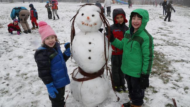 Maya, Coen and Leo make a snowman at Olinda. Picture: David Crosling