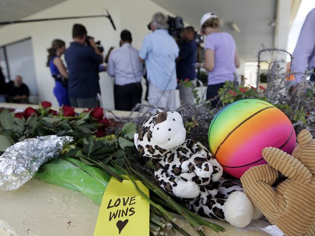 Flowers and stuffed animals are left at the scene of a deadly shooting outside the Club Blu nightclub. Picture: AP Photo/Lynne Sladky