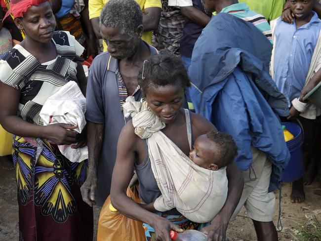 A woman carrying her child stands in a queue to receive food from World Food Programme in Nhamatanda, about 100km west of Beira. Picture: AP