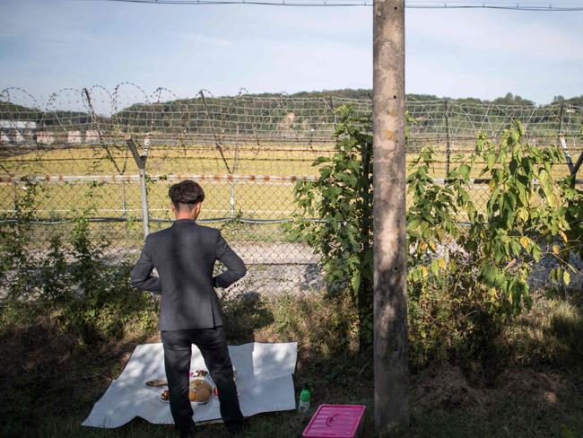 A North Korean refugee prepares to perform a ceremonial offering to relatives in North Korea, near the Demilitarized Zone at Imjingak. Picture: AFP