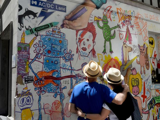 People look at artwork on AC/DC Lane in Melbourne after the announcement of the death of Malcolm Young. Picture: AFP