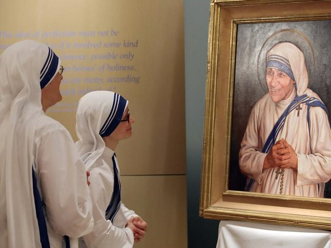 Sisters of the Missionaries of Charity look at an official canonisation portrait of Mother Teresa. Picture: AFP