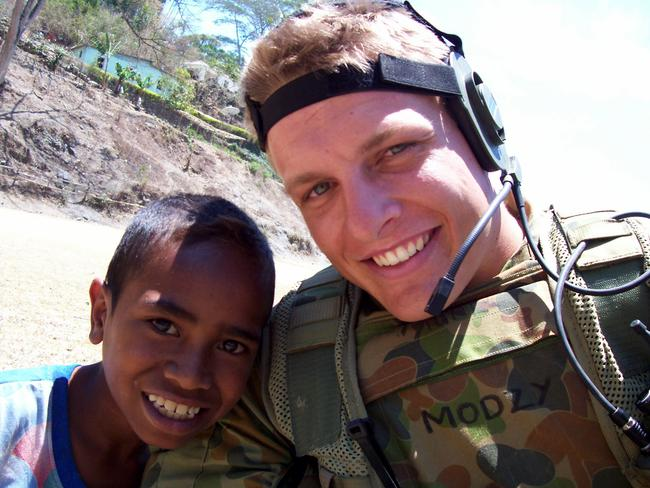 Matthew Model with a local boy in East Timor, during his military service. Picture: Nathan Edwards