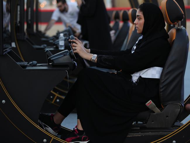 A young woman wearing tries out a driving simulator at an outdoor educational driving event for women on June 23, 2018 in Jeddah, Saudi Arabia. Picture: Getty