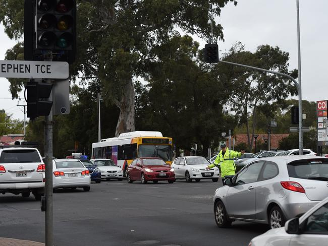 Police direct traffic at the corner of Stephen Tce and Payneham Rd due to the stop lights being down. Picture: Naomi Jellicoe