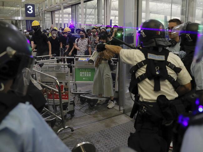 Policemen in riot gear face protesters at the main entrance of Hong Kong airport on Tuesday. Picture: AP/Kin Cheung