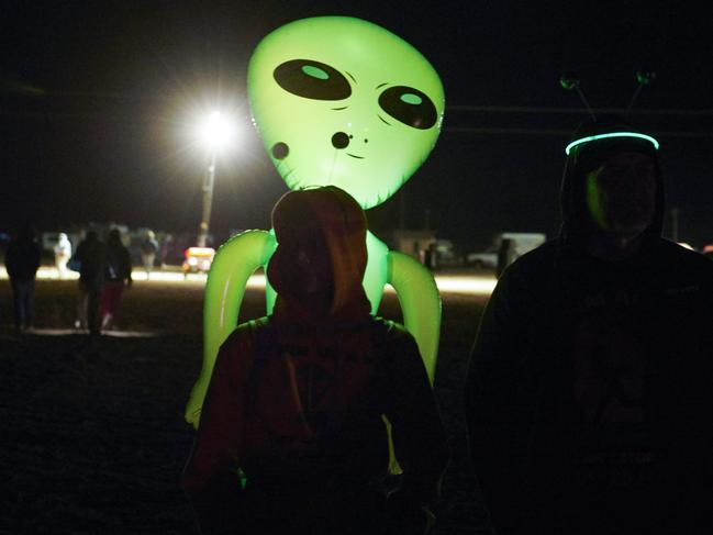 "A small group of alien-hunters gather to ""storm"" Area 51 at an entrance to the military facility. Picture: Bridget BENNETT / AFP"