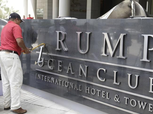 A man removes the word Trump from the Trump Ocean Club International Hotel and Tower in Panama City on Monday after he ceded control of the property. Picture: AP Photo/Arnulfo Franco