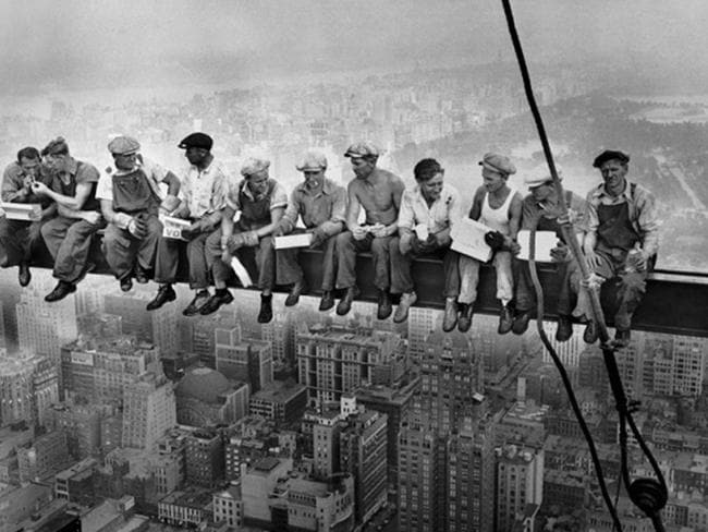 Workmen relax and eat their lunch on a girder at the Rockefeller Centre in New York in the famous photo, 'Lunch Atop A Skyscraper', by Charles Ebbets in 1932.