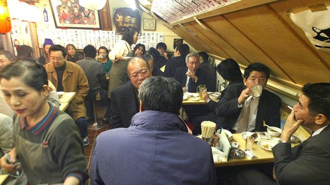 Japanese salarymen pack a pub in Tokyo's business district in the evening.