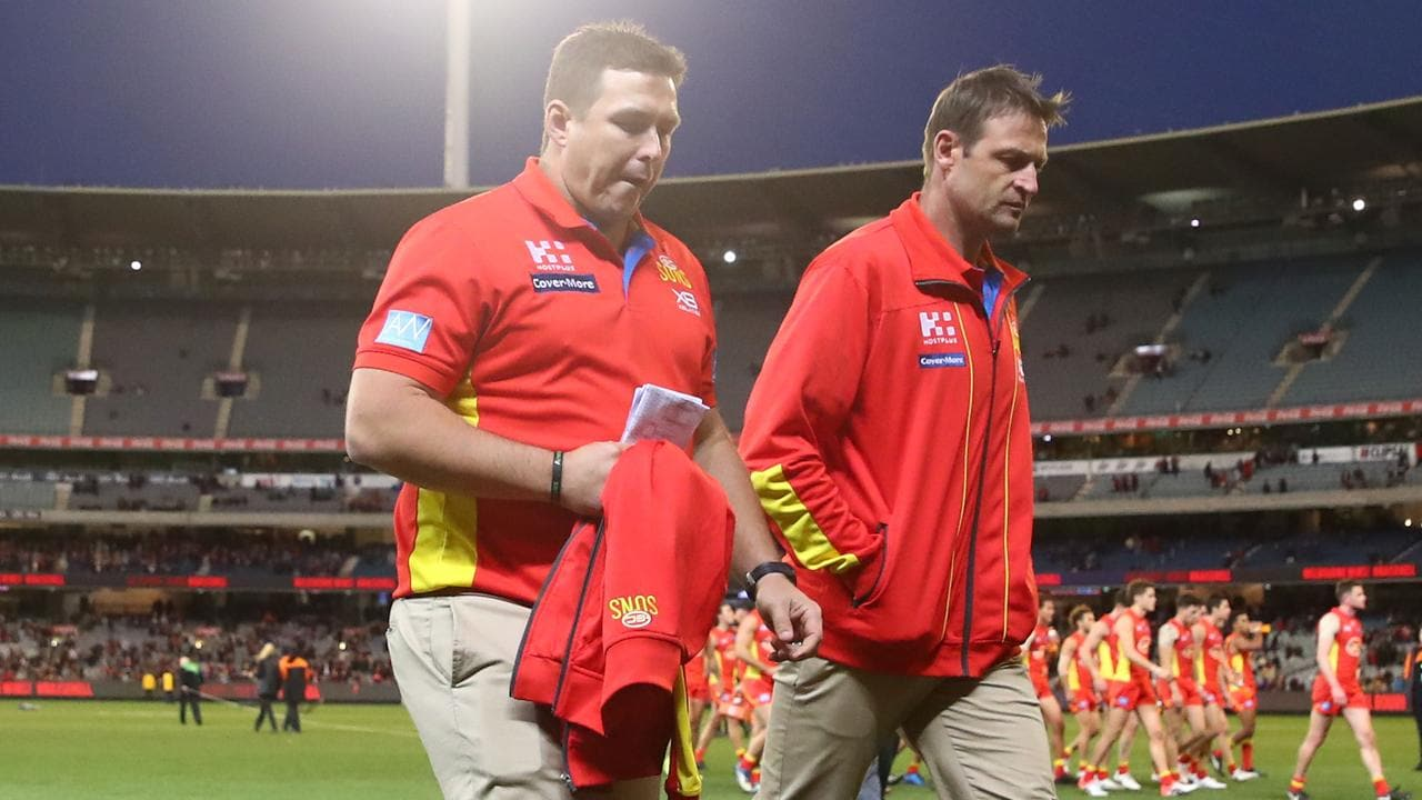 Suns coach Stuart Dew and assistant coach Matthew Primus leave the field after losing to Melbourne. Photo: Scott Barbour/AFL Media/Getty Images
