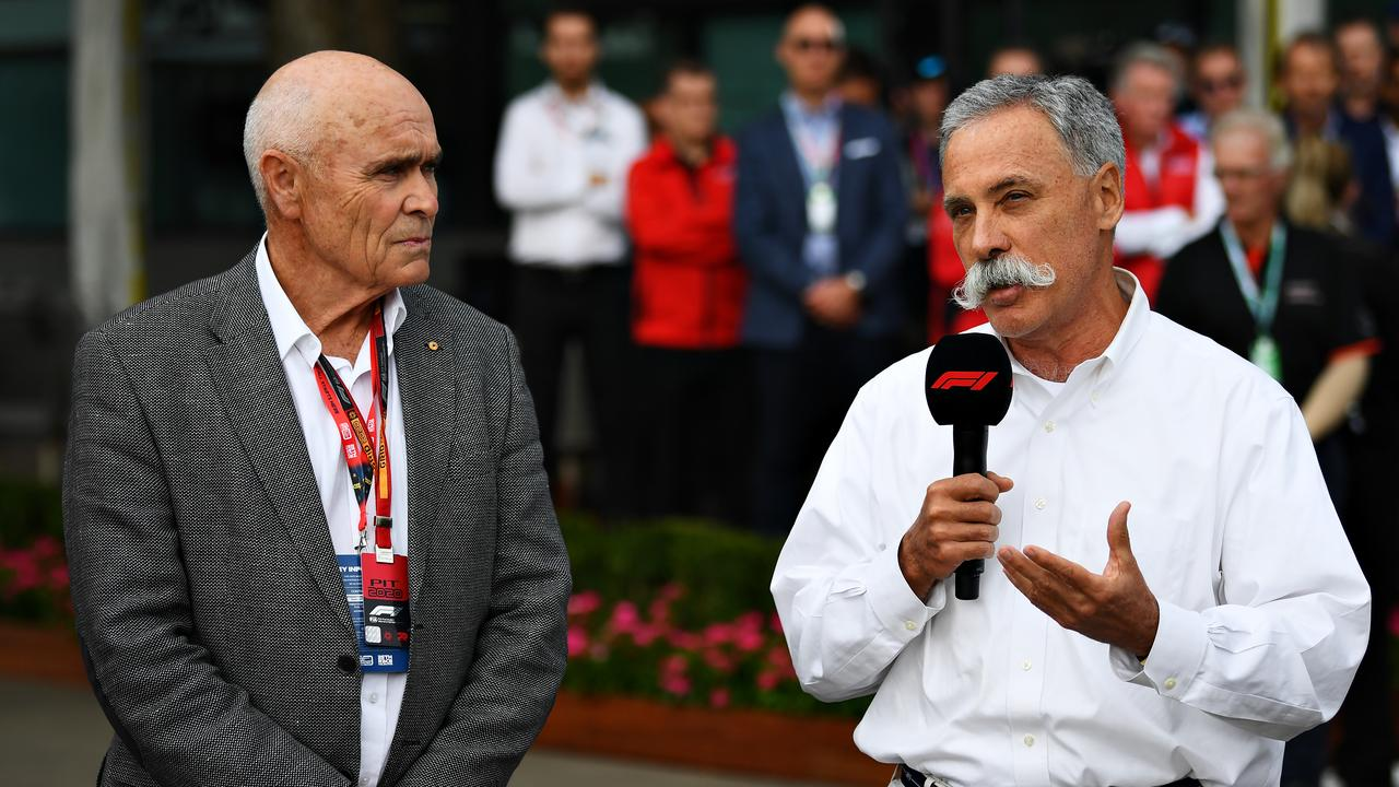 (R-L) Chase Carey talks next to Paul Little as a press conference is held outside the paddock.