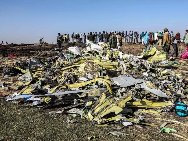 People stand near collected debris at the crash site of the Ethiopian Airlines plane near Bishoftu. Picture: AFP