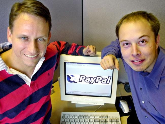 PayPal Chief Executive Officer Peter Thiel and founder Elon Musk pose with the PayPal logo at corporate headquarters in Palo Alto, California in 2000.