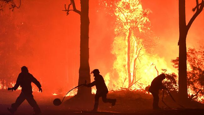 RFS volunteers and NSW Fire and Rescue officers fight a bushfire encroaching on properties near Termeil on the Princes Highway between Batemans Bay and Ulladulla. Picture: AAP Image/Dean Lewins