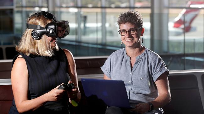Angelique Foran and Dr Emma Johnston try out the treatment, which involves the patient strapping on a headset to place themselves in the middle of a virtual airport or plane to help solve the anxiety they feel when flying. Picture: Calum Robertson