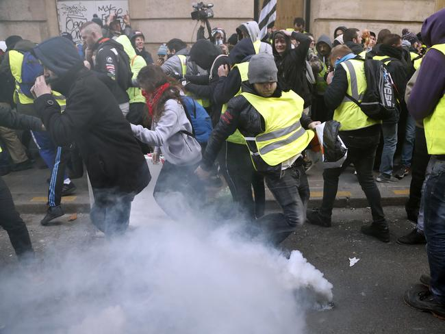 A teargas canister falls among demonstrators wearing yellow vests. Picture: AP